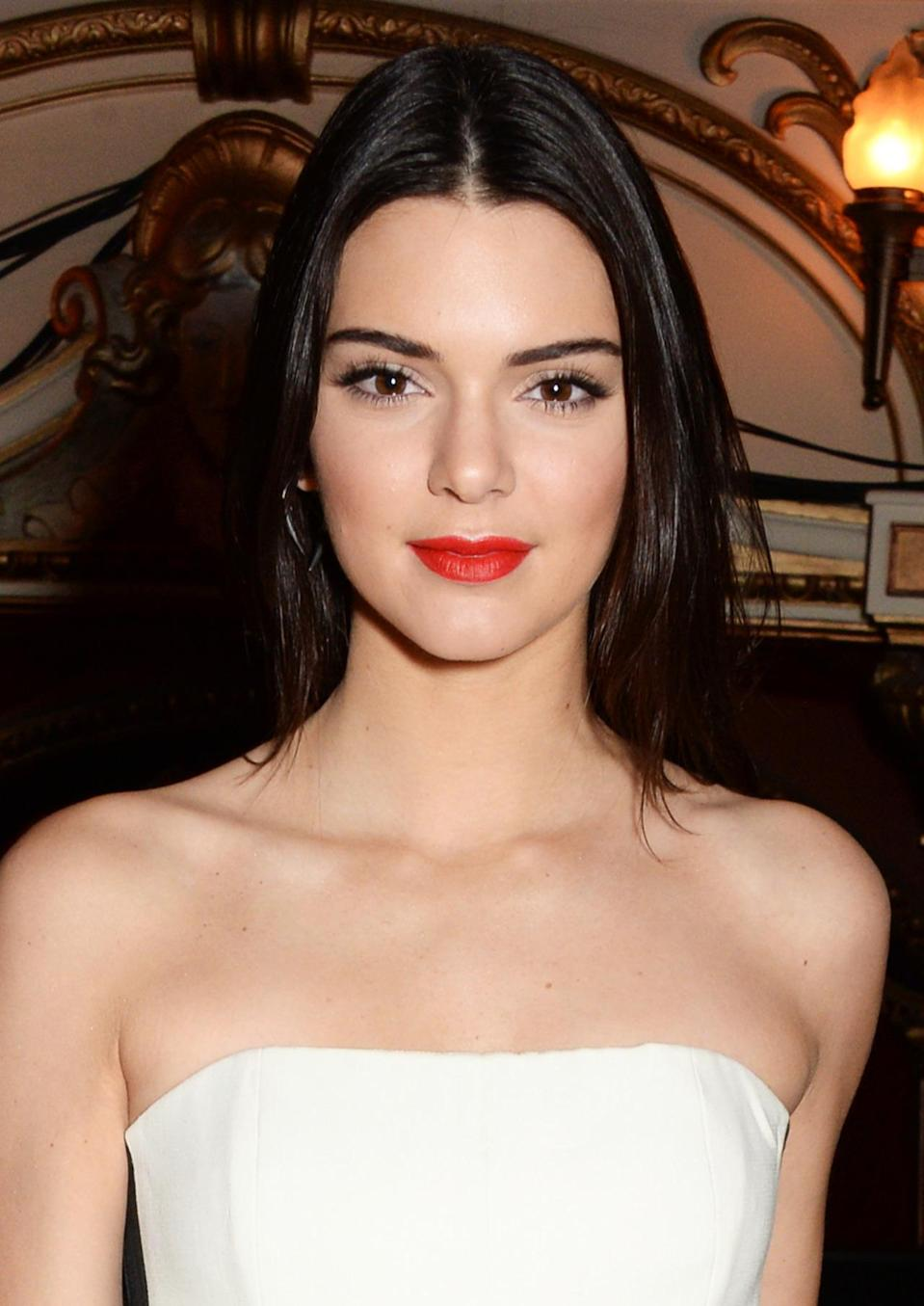 <p>At a reception for the British Fashion Awards in London, Jenner's simple nighttime look consisted of orange-red lipstick, light bronzer, and straightened hair. <i>(Photo: Getty Images)</i></p>