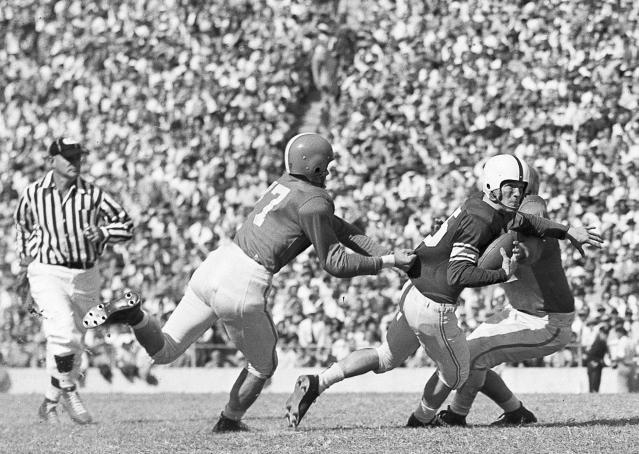 FILE - In this Oct. 13, 1951, file photo, Texas tackle Bill Wilson (77) grabs a shirt as tackle Charles Petrovich, right, goes for the ball as they throw Oklahoma halfback Billy Vessels for a 10-yard loss on a lateral pass play in the first quarter of a college football at the Cotton Bowl in Dallas. No. 5 Oklahoma and No. 9 Texas are playing in a rare Red River rivalry rematch in the Big 12 championship game on Saturday. It is the first time in 115 years that the border state rivals will play twice in the same season. (AP Photo/Bob Scott, File)