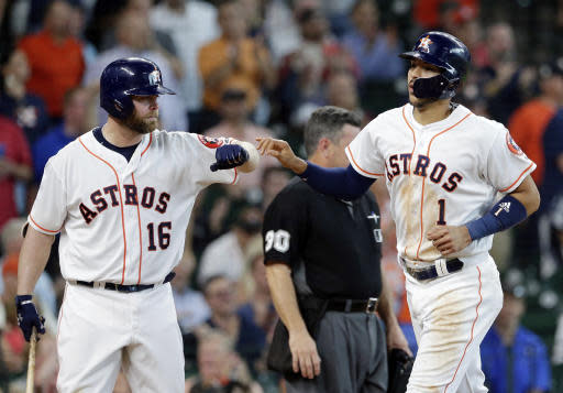 Houston Astros Brian McCann (16) congratulates Carlos Correa (1) after he scored on a hit by Yuli Gurriel during the fourth inning of a baseball game against the San Francisco Giants Wednesday, May 23, 2018, in Houston. (AP Photo/Michael Wyke)