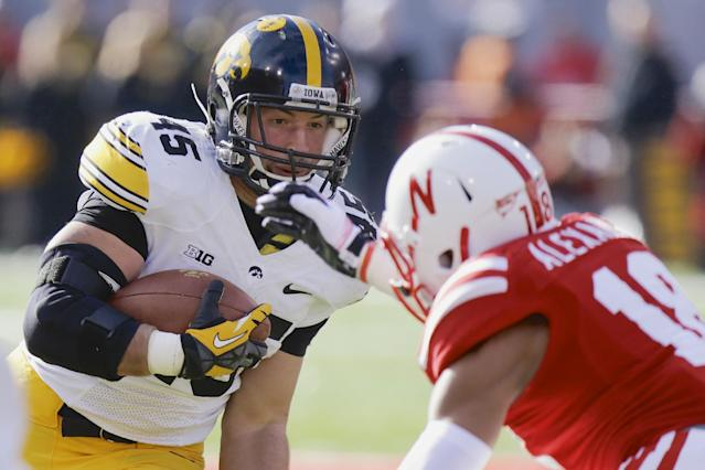Iowa running back Mark Weisman (45) carries the ball against Nebraska safety LeRoy Alexander (18) during the first half of an NCAA college football game in Lincoln, Neb., Friday, Nov. 29, 2013. (AP Photo/Nati Harnik)