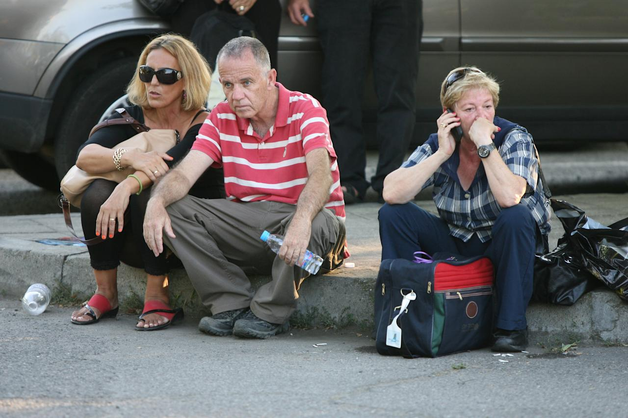 Passengers sit beside the road shortly after an explosion near Burgas airport, outside the Black Sea city of Burgas, Bulgaria, some 400 kilometers (250 miles) east of the capital, Sofia, Wednesday, July 18, 2012. A bus carrying young Israeli tourists in a Bulgarian resort exploded Wednesday, killing three people and wounding at least 20, police said. Witnesses told Israeli media that the huge blast occurred soon after someone boarded the vehicle. (AP Photo/ Impact press Group)