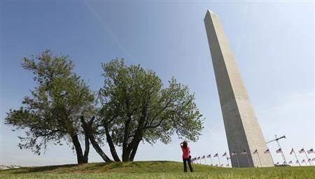 A woman stops to photograph the re-opened Washington Monument in Washington