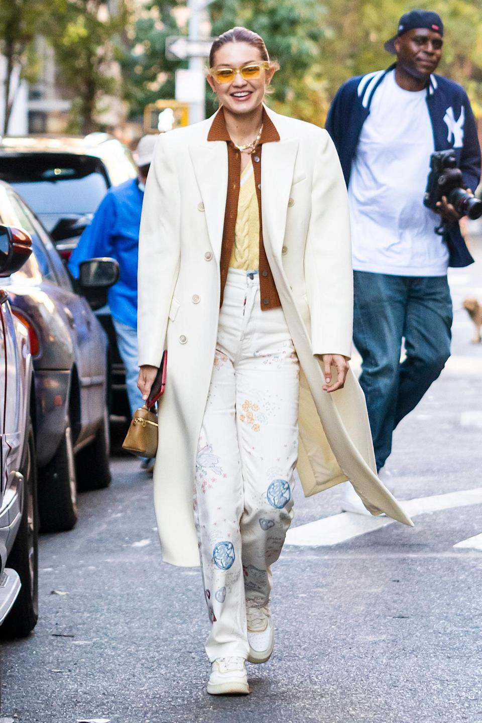 <p>Gigi Hadid sports a long white coat with a stylish pair of yellow sunglasses while out in Soho on Oct. 11 in N.Y.C. </p>