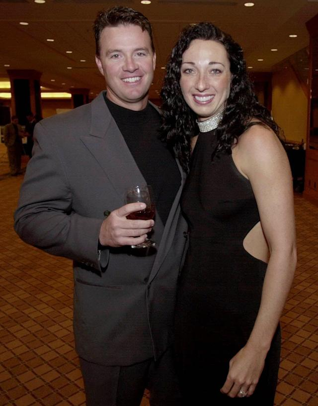 FILE - In this March 1, 2001 file photo, Six-time Olympic gold medalist swimmer Amy Van Dyken, right, and Denver Broncos punter Tom Rouen pose before going into the Colorado Sports Hall of Fame dinner in Denver. Van Dyken has a severed spine after an accident on her all-terrain vehicle in Arizona. A hospital spokeswoman didn't provide details Monday on the injuries. The swimmer was hurt Friday night, June 6, 2014, and told emergency workers at the scene she could not move her toes or feel anything touching her legs. (AP Photo/David Zalubowski, File)