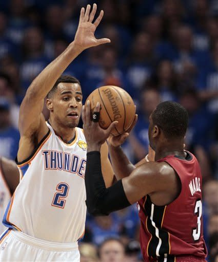 Miami Heat shooting guard Dwyane Wade is defended by Oklahoma City Thunder shooting guard Thabo Sefolosha (2) of Switzerland during the first half at Game 1 of the NBA finals basketball series, Tuesday, June 12, 2012, in Oklahoma City. (AP Photo/Jeff Roberson)