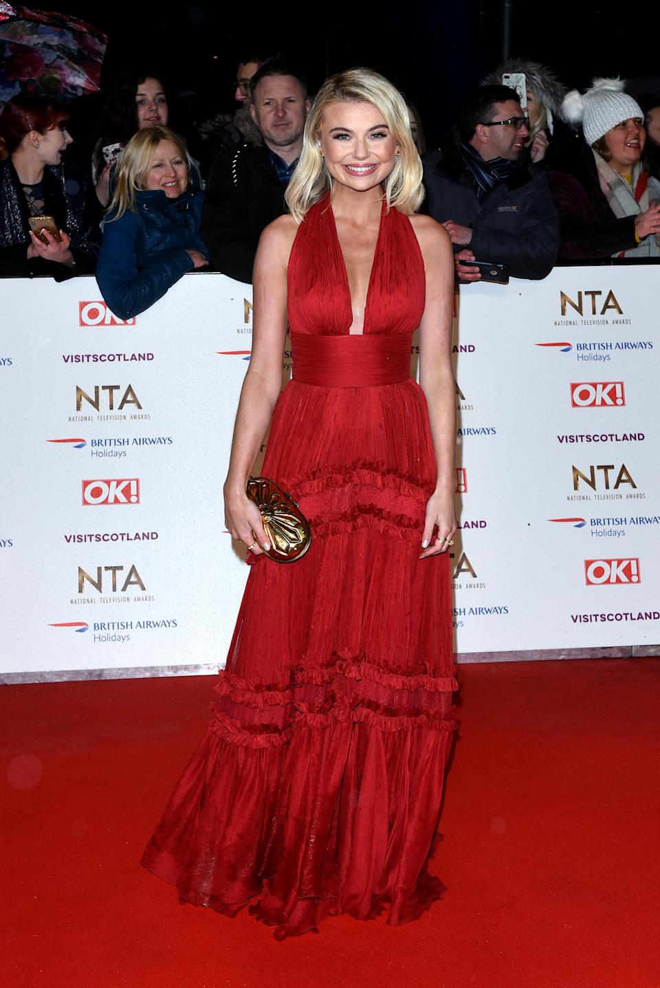 <p>Wearing a red halterneck gown with a gold clutch. <em>[Photo: Getty]</em> </p>