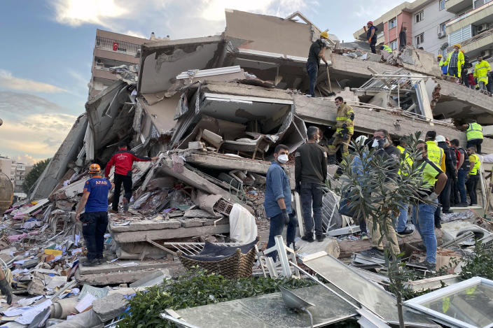 Rescue workers try to save people trapped in the debris of a collapsed building, in Izmir, Turkey, Friday, Oct. 30, 2020. A strong earthquake struck Friday in the Aegean Sea between the Turkish coast and the Greek island of Samos, killing several people and injuring hundreds amid collapsed buildings and flooding, officials said.(AP Photo/Ismail Gokmen)