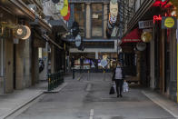 A lone shopper walks down the usually busy Degraves Street laneway fame for its cafe's and coffee during lockdown in Melbourne, Australia, Wednesday, Aug. 5, 2020. Victoria state, Australia's coronavirus hot spot, announced on Monday that businesses will be closed and scaled down in a bid to curb the spread of the virus. (AP Photo/Asanka Brendon Ratnayake)