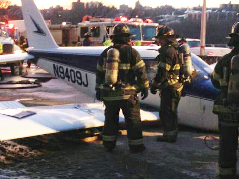 In this photo downloaded from the New York City Fire Department's Twitter account, firefighters stand near a light airplane that made an emergency landing on the Major Deegan Expressway in the Bronx borough of New York, Saturday, Jan. 4, 2014. Fire officials say all were taken to a hospital, but there have been no immediate reports of serious injuries. (AP Photo/New York City Fire Department)