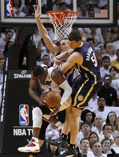 Miami Heat's Dwyane Wade, lower left, loses the ball after Indiana Pacers' Tyler Hansbrough (50) committed a flagrant foul during the first half of Game 5 of an NBA basketball Eastern Conference semifinal playoff series, in Miami, onTuesday, May 22, 2012. At rear is Pacers' Lou Amundson. (AP Photo/Lynne Sladky)