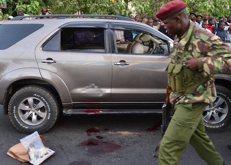 A police officer walks past the blood-stained vehicle of prominent MP George Muchai in Nairobi after he was shot dead along with his two bodyguards and his driver by gunmen on February 7, 2015