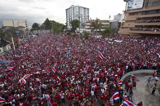 Costa Rica soccer fans fill the street as they celebrate their team's victory over Greece at a Brazil World Cup round of 16 game in San Jose, Costa Rica, Sunday, June 29, 2014. Costa Rica won a penalty shootout 5-3 after the match ended 1-1 following extra time. (AP Photo/Esteban Felix)