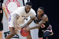 Abilene Christian forward Airion Simmons (3) and Lamar guard Davion Buster (13) battle for a loose ball during the second half of an NCAA college basketball game in the Southland Conference semifinals Friday, March 12, 2021, in Katy, Texas. (AP Photo/Michael Wyke)