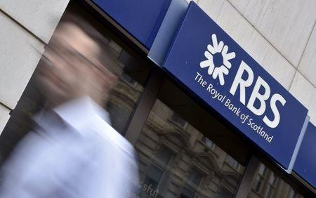 A man walks past a branch of The Royal Bank of Scotland (RBS) in central London in this August 27, 2014 file photo. REUTERS/Toby Melville/Files