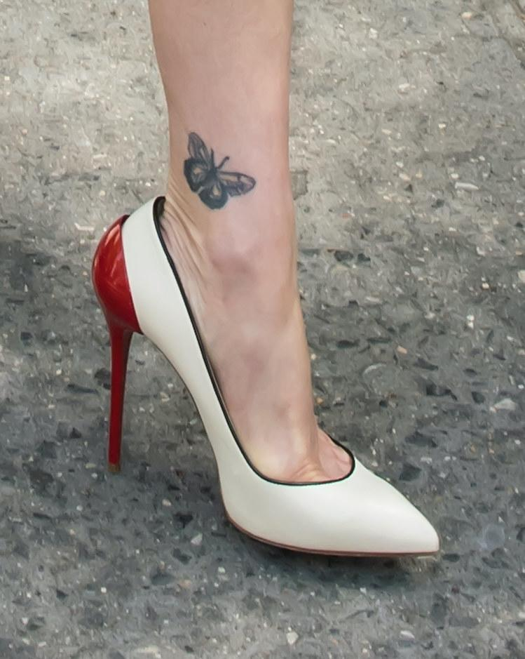 A person wearing high heels with a butterfly tattoo on their ankle