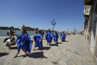 Participants in fish costumes perform on a protest event of the environmental protection movement Animal Rebellion during the G20 Economy and Finance ministers and Central bank governors' meeting in Venice, Italy, Saturday, July 10, 2021. (AP Photo/Luca Bruno)