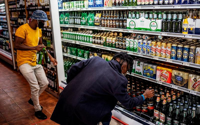 Customers buy alcohol at a liquor shop at the Bara taxi rank in Soweto, Johannesburg - AFP