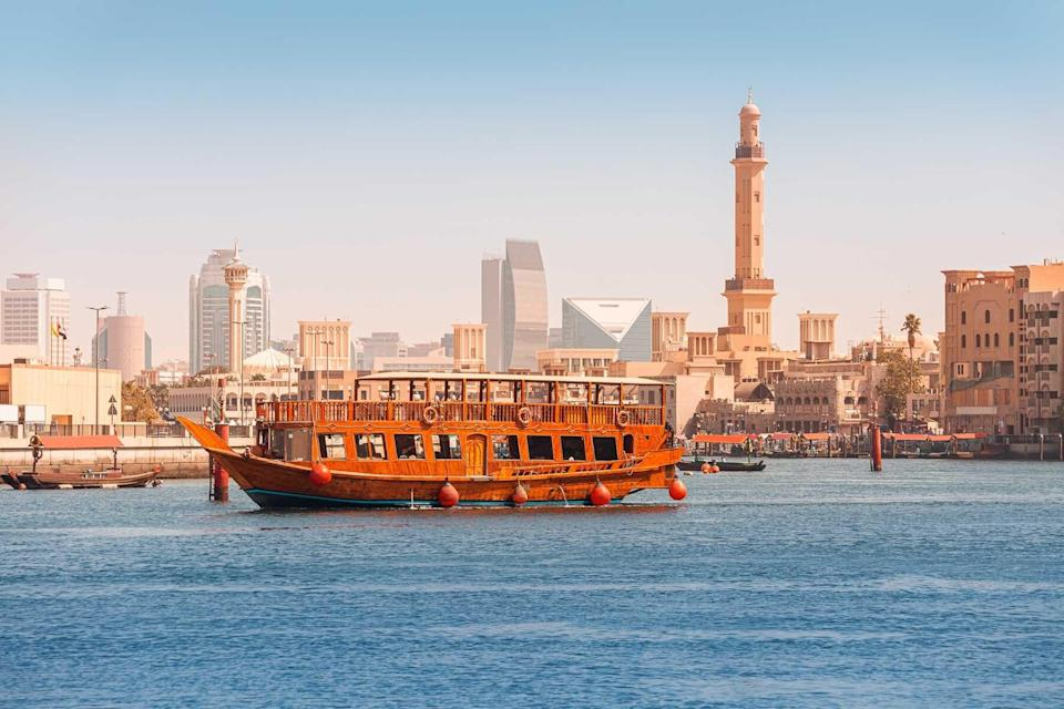 An authentic wooden cruise ship cruises and transports tourists along the Dubai Creek Canal with skyscrapers and minarets of mosques in the background. Travel and sightseeing
