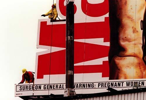 A color photograph shows workers in harnesses removing a portion of a Marlboro billboard