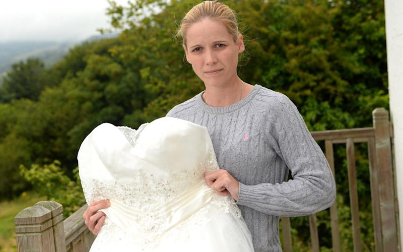 Melanie Bishop, who tricked brides into thinking they were buying bespoke gowns, with one of the dresses - WALES NEWS SERVICE