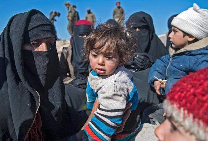 Fully veiled women and children gather after fleeing from the Baghouz area in the eastern Syrian province of Deir Ezzor on February 12, 2019 during an operation by the US-backed Syrian Democratic Forces (SDF) against the Islamic State group (AFP Photo/Fadel SENNA)