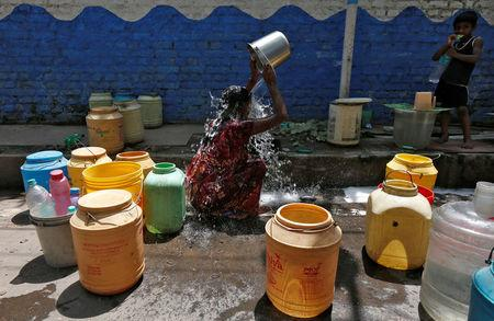 A woman bathes at a roadside municipal tap in a slum area on a hot summer day on the outskirts of Kolkata, India, April 22, 2016. REUTERS/Rupak De Chowdhuri