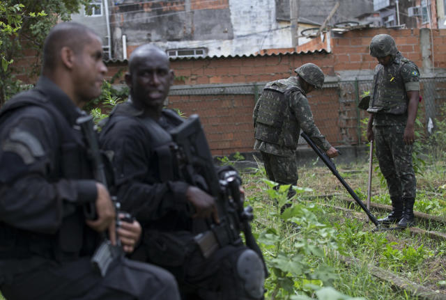 "Special Police Operations Battalion (BOPE) officers stand guard, as army soldiers look for weapons with the aid of a metal detector during an operation in the Mare slum complex, ahead of its ""pacification,"" in Rio de Janeiro, Brazil, Wednesday, March 26, 2014. Elite federal police and army troops will be sent to the city to help quell a wave of violence in so-called ""pacified"" slums. Recent attacks on police bases in the favelas is raising concerns about an ambitious security program that began in 2008, in part to secure the city ahead of this year's World Cup and the 2016 Olympics. (AP Photo/Silvia Izquierdo)"