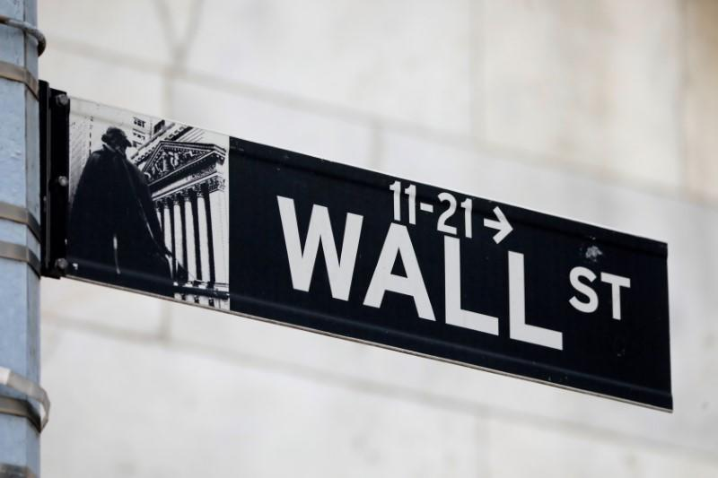 FILE PHOTO: A street sign for Wall Street is seen outside of the New York Stock Exchange (NYSE) in New York City