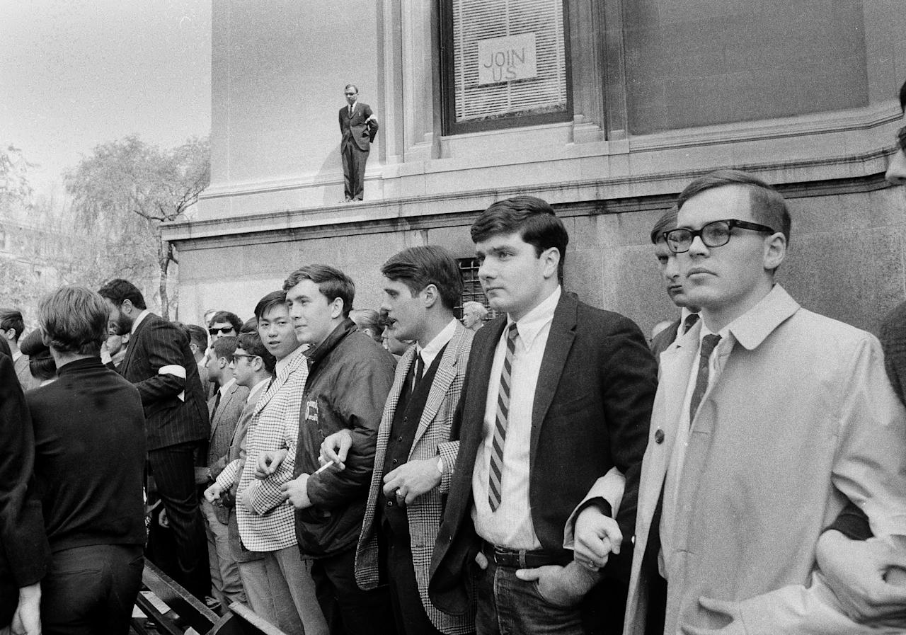 FILE – In this April 29, 1968 file photo, Columbia University students who don't agree with their classmates staging a sit-in in Low Memorial Library on the school campus in New York form a human blockade around the building, to prevent food and supplies from reaching the demonstrators. Fifty years ago, students occupied five buildings at the university and shut down the Ivy League campus in a protest over the school's ties to a military think tank and what protesters saw as racism toward Columbia's Harlem neighbors. More than 700 protesters were arrested and more than 130 were injured when police retook the occupied buildings, during what was part of a year of global turmoil.(AP Photo/Anthony Camerano, File)