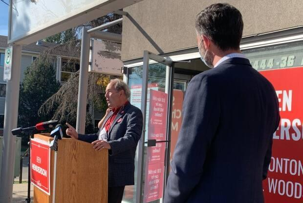 Liberal candidate Ben Henderson speaks to media outside his campaign office in Mill Woods Tuesday as Mayor Don Iveson lends support to long-time city council colleague.  (Dave Bajer/CBC - image credit)