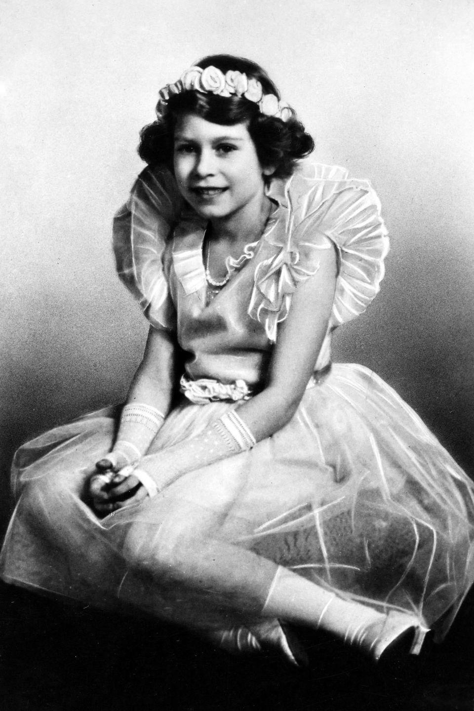 <p>In an adorable ballerina outfit with a floral crown and fingerless gloves. At the time of this photograph, she was Princess Elizabeth, daughter of The Duke and Duchess of York.</p>