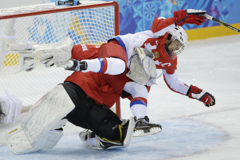 Yekaterina Smolentseva of Russia collides with Goalkeeper Florence Schelling of Switzerland during the 2014 Winter Olympics women's ice hockey quarterfinal game at Shayba Arena, Saturday, Feb. 15, 2014, in Sochi, Russia. (AP Photo/Matt Slocum)