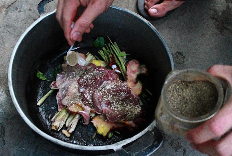 A cook prepares a dish made with cat meat at a restaurant in Hanoi on May 13, 2014 (AFP Photo/)