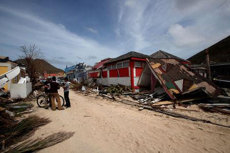 Residents stand in front of houses destroyed by Hurricane Irma during the visit of France's President Emmanuel Macron in the French Caribbean islands of St. Martin September 12, 2017. Picture taken September 12, 2017. REUTERS/Christophe Ena/Pool
