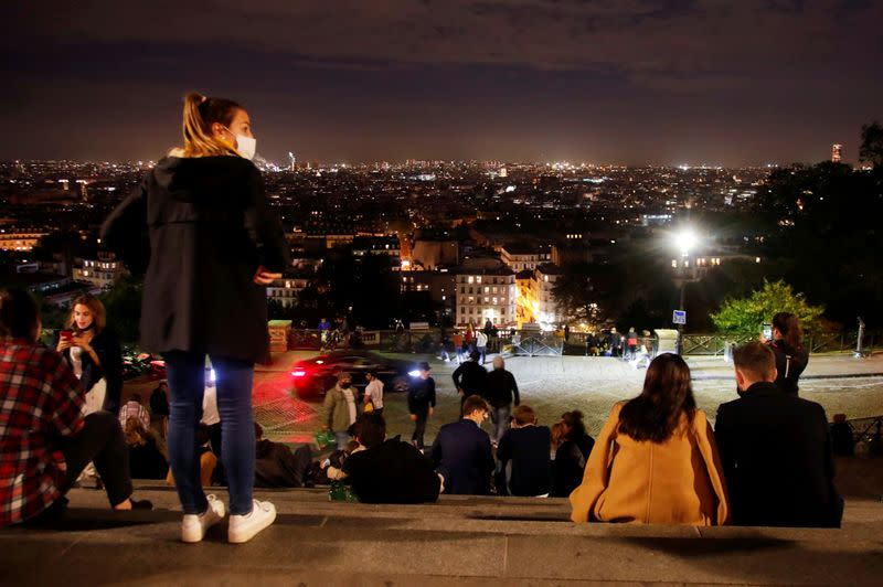FILE PHOTO: People enjoy the view from Montmartre a few minutes before the nightly curfew imposed to curb the spread of the coronavirus, in Paris