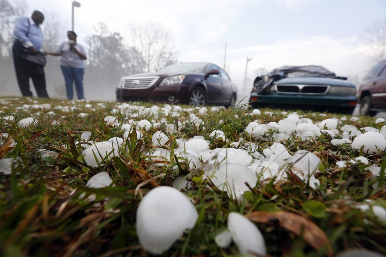 Golfball sized hail litter the ground by Andrew Stamps and his wife Valorie as they prepare to cover their shattered rear window of her 2009 Toyota Avalon in Pearl, Miss., Monday, March 18, 2013, following a hailstorm that hit communities throughout central Mississippi. The National Weather Service in Jackson says there were a few super cells in central Mississippi and reports of hail up to baseball size in Clinton, golf ball and tennis ball sized in Pearl and Brandon and quarter sized in downtown Jackson, Miss. The Mississippi Emergency Management Agency says severe weather has caused damage in at least 10 counties as the storms moved through parts of the state. (AP Photo/Rogelio V. Solis)