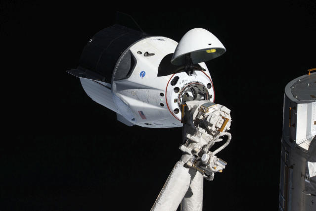 In this March 4, 2019 photo made available by NASA, the uncrewed SpaceX Crew Dragon spacecraft, with its nose cone open to expose the docking mechanism, approaches the International Space Station's Harmony module. It was the first Commercial Crew vehicle to visit the ISS. (NASA via AP)