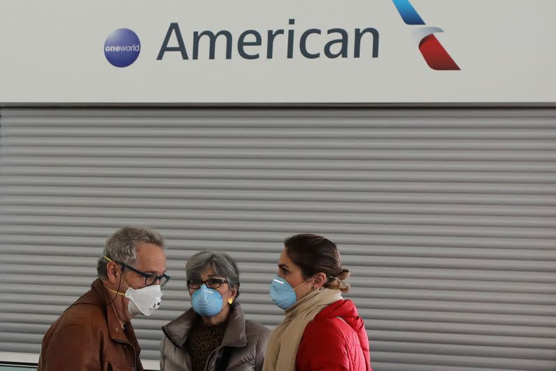 Passengers wear protective face masks as they stand in front of the American Airlines ticketing desk at Josep Tarradellas Barcelona-El Prat Airport, after further cases of coronavirus were confirmed in Barcelona