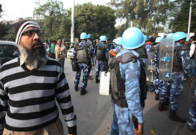 A protester stand near police security officials during a demonstration against India's new citizenship law CAA ( Citizenship amandment Act ) in Allahabad on December 19,2019 . Indians defied bans nationwide as anger swells against a citizenship law seen as discriminatory against muslims, following days of protest, clashes, and riots that have left six dead .(Photo by Ritesh Shukla/NurPhoto via Getty Images)