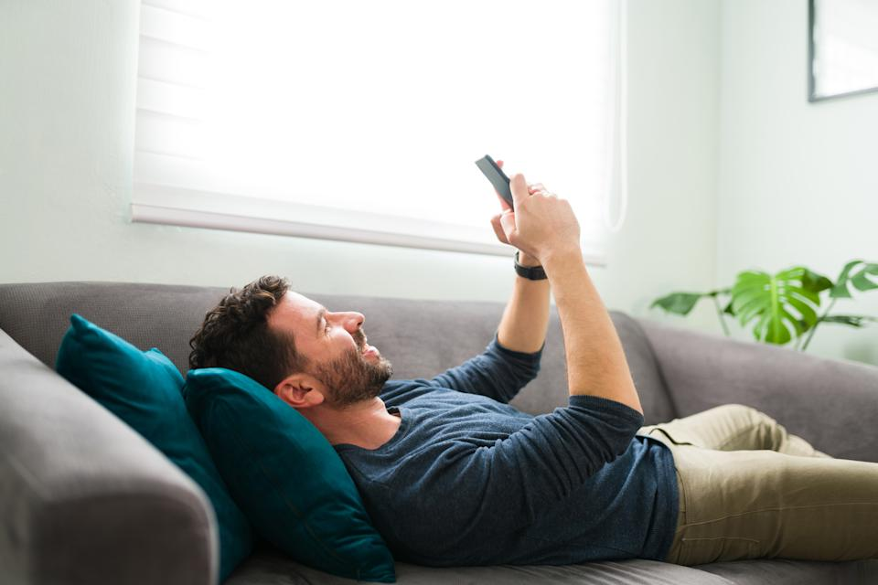 Hispanic guy in his 30s lying on the couch and texting with his girlfriend. Handsome man is happy and smiling with his smartphone