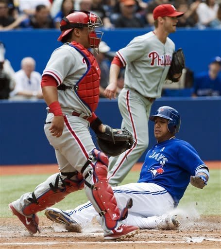 Toronto Blue Jays' Yunel Escobar slides into home plate on a single by Rajai Davis against the Philadelphia Phillies during the fourth inning of a baseball game, Sunday, June 17, 2012, in Toronto. (AP Photo/The Canadian Press, Aaron Vincent Elkaim)