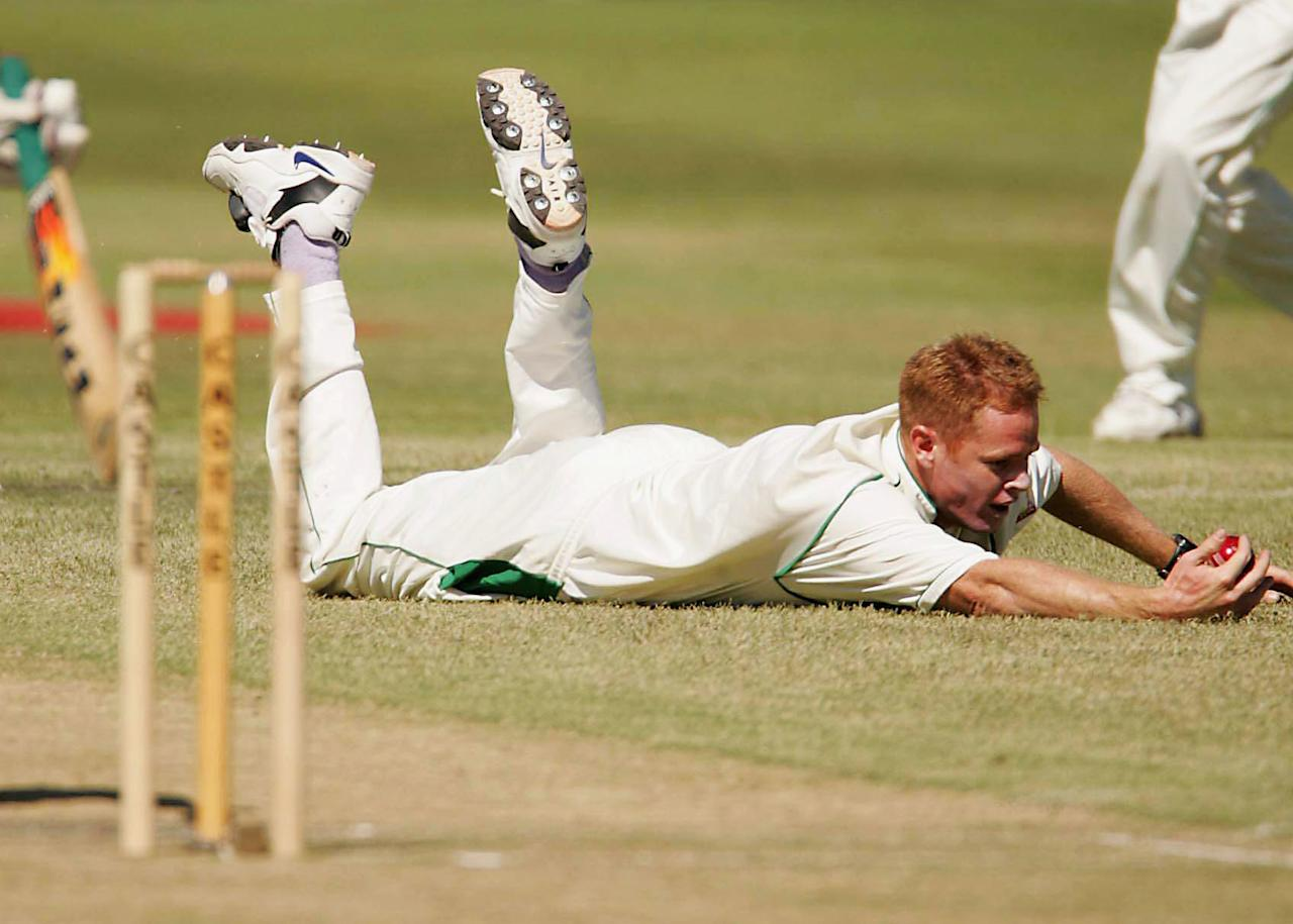 NEWLANDS, SOUTH AFRICA - MARCH 5:  (TOUCHLINE PHOTO IMAGES ARE AVAILABLE TO CLIENTS IN THE UK, USA AND AUSTRALIA ONLY) Shaun Pollock of South Africa dives to take a catch during day two of the first test against Zimbabwe at Newlands March 5, 2005 in Cape Town, South Africa. (Photo by Touchline Photo/Getty Images)