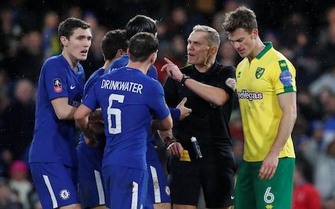 Danny Drinkwater, Alvaro Morata and Andreas Christensen react after Willian is shown a yellow card for simulation by referee Graham Scott  - Credit: Reuters