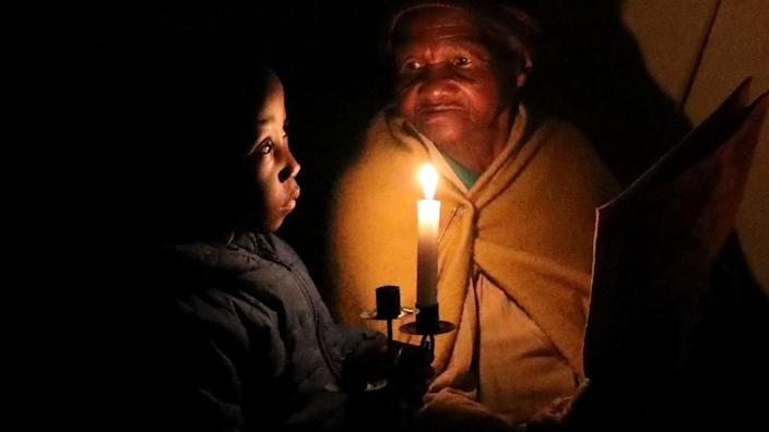 A woman and her great-grandson sit in candlelight.