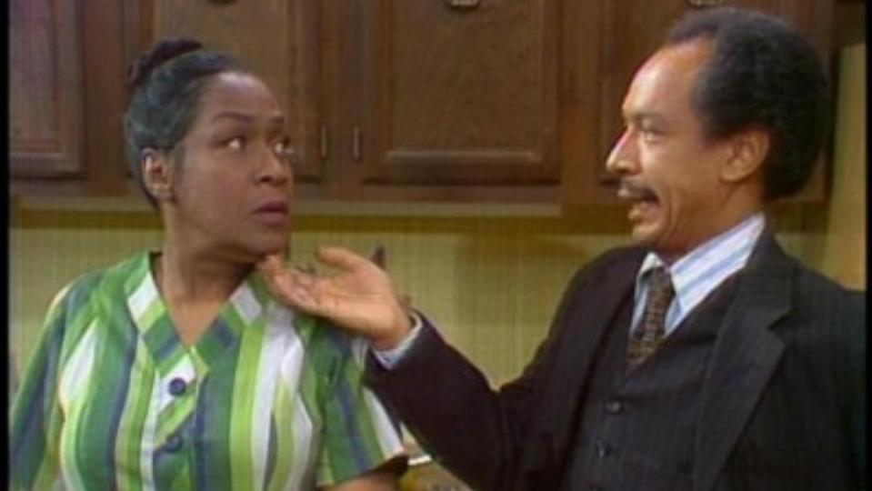a photo of george jefferson wearing a brown suit standing beside weezy jefferson with a green dress
