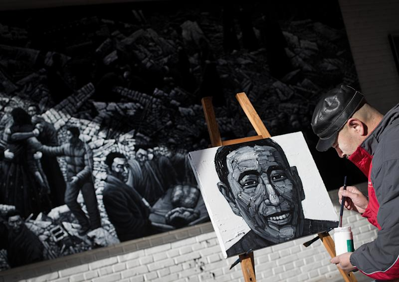 In this photo taken on Tuesday, Dec. 25, 2012, Beijing-based artist Liu Yi paints a portrait of a Tibetan who has self-immolated over the past three years, at his studio in Songzhuang art village in Tongzhou, on the outskirt of Beijing. Liu is working on a series of black-and-white portraits he knows will never be shown in a Chinese gallery. His varied subjects - men and women, young and old, smiling and pensive - have one thing in common: They are Tibetans who have set themselves on fire to protest repressive Chinese rule. (AP Photo/Andy Wong)