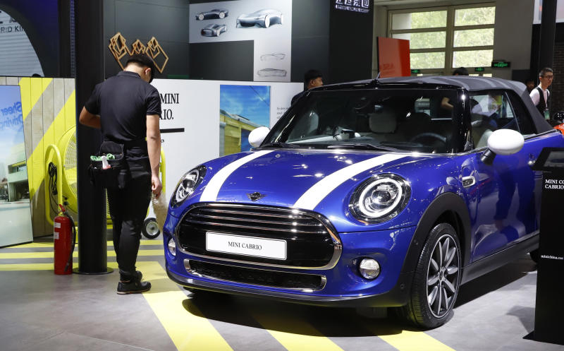 In this April 26, 2018, photo, cleaners wait near a MINI Cooper Cabrio displayed at the China Auto Show in Beijing. BMW Group and China's biggest SUV brand, Great Wall Motor, announced Tuesday, July 10, 2018, a partnership to produce electric MINI vehicles in China. (AP Photo/Ng Han Guan)