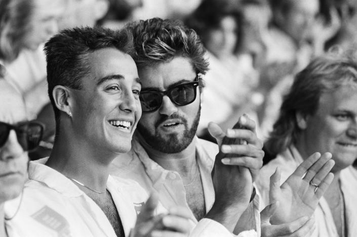 Live Aid dual venue benefit concert held on 13th July 1985 at Wembley Stadium in London, England, and the John F Kennedy Stadium in Philadelphia, Pennsylvania, United States, the concerts were organised as a follow up to the Band Aid single 'Do They Know Its Christmas?', the brainchild of Bob Geldof and Midge Ure, to raise money for victims of the famine in Ethiopia,Picture shows Wham duo Andrew Ridgeley and George Michael watching the concert at Wembley. (Photo by Mike Maloney/Daily Mirror/Mirrorpix/Getty Images)
