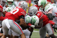 Oregon running back Travis Dye, center, is tackled by Ohio State linebackers Cody Simon, left, and Teradja Mitchell during the first half of an NCAA college football game Saturday, Sept. 11, 2021, in Columbus, Ohio. (AP Photo/Jay LaPrete)