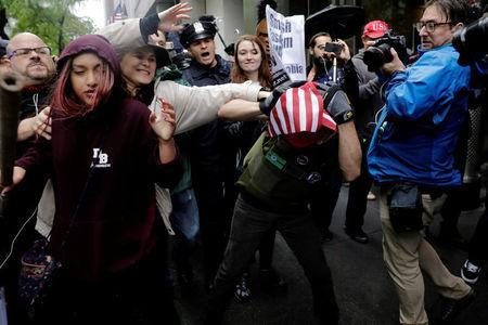 Anti-Trump demonstrators (L) grapple over a U.S. flag with demonstrators protesting against CUNY's decision to allow Linda Sarsour, a liberal, Palestinian-American political activist, to speak at this year's commencement in New York, U.S., May 25, 2017. REUTERS/Lucas Jackson
